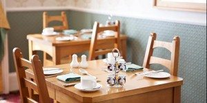 Wooden Breakfast dining table with coffee and placements at Hazelwood Guesthouse York