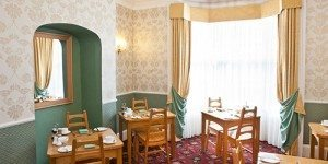 Dining room with wooden chairs and tables for breakfast at Hazelwood Guesthouse York
